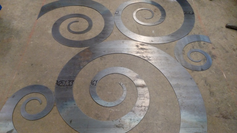 The CNC machine plasma cuts out the vector spiral pieces.